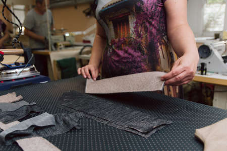 A woman strokes the fabric for further sewing. Tailor ironing clothes with industrial iron.