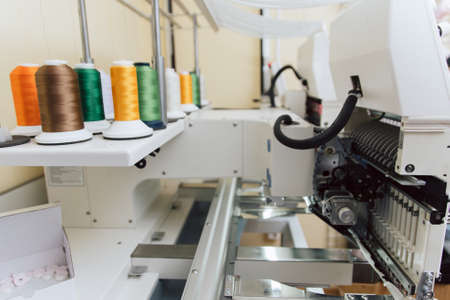colored thread on the sewing machine. industrial embossing text on fabric. many threads on industrial sewing machine. industrial fabric production Stock Photo