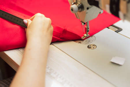 Tailor measures fabric with a ruler. Woman works in a garment factory. a tailor embroiders with a sewing machine on a crocheted fabric.