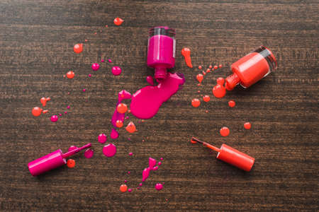 Spilled orange and pink nail polishes on wooden background. nail polish drops. Blot of nail polish on wooden background. Nail Polish splatter.