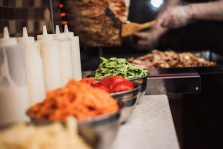 Drinks with tomatoes, cucumbers, Korean carrots and french fries, sauce dishes on the background of kebabs and fried chicken meat for shawarma. Cooking shawarma and burrito. Stock Photo