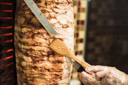 Cooking shawarma and ciabatta in a cafe. A man in disposable gloves cuts meat on a skewer. A cook cuts a large-sized chicken kebab