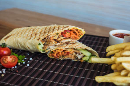 shawarma and french fries with sauce lies on a dark bamboo background. Eastern fast food. Beautiful photo with coarse salt, cherry tomatoes, ciabatta and French fries with ketchup in a cafe.
