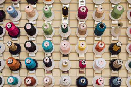 Garnrollen hängen in einer Schneiderei. Stränge für Nähmaschinen hängen in einer Nähwerkstatt. Foto schließen. Standard-Bild