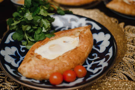 Adjara khachapuri on the eastern table. fresh egg in hot bread on oriental plates is in a restaurant. Stock Photo