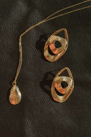 Stylish women's gold jewelry and jewelry on a leather background. Fashionable pendant and earrings in a vertical photo.