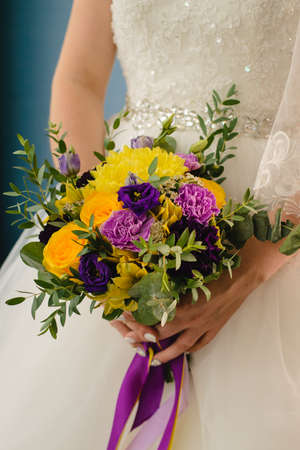 Bridal bouquet on the wedding day. A lovely girl holds a bouquet of yellow roses and purple flowers.
