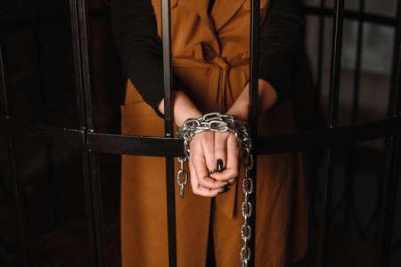 Verbrecher, Hände in Ketten, Frau hinter Gittern
