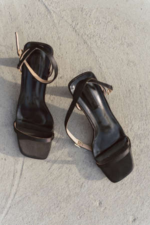 Black leather open sandals with heels stand on the asphalt in the sun. Women's shoes with buckles without anyone. Vertical photo of stylish and fashionable high heel shoes.