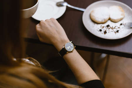 girl looks at the clock in a cafe over a cup of coffee. time on the clock - the time for breakfast, dessert or eating sweets for tea.