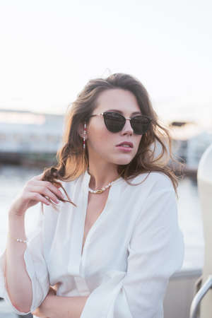 A beautiful girl in dark sunglasses and with beautiful styling is standing on the pier by the river. Girl in pearl jewelry and glasses.