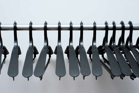 black plastic hangers hang on a light background. many different hangers. floor coat rack.