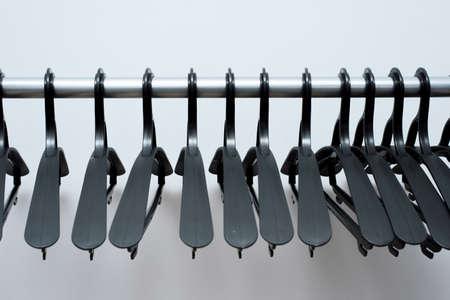 des cintres en plastique noir sont suspendus sur un fond clair. beaucoup de cintres différents. porte-manteau au sol.