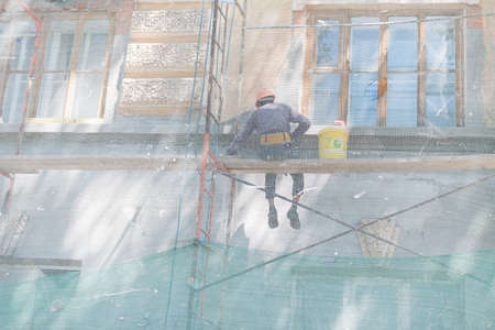 A man sits on a scaffold and restores the building. The builder paints the walls of the building and the facade at a height.