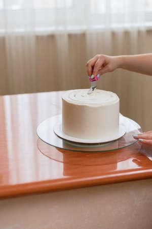 La niña exprime la crema sobre el pastel. Una niña encantadora haciendo un pastel en una panadería. La niña alisa la crema sobre el pastel. Pastel blanco sobre una mesa de madera