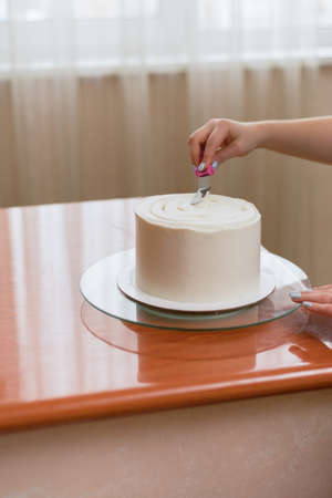 The girl squeezes the cream on the cake. A lovely girl making a cake in a bakery. The girl smoothes the cream on the cake. White cake on a wooden table
