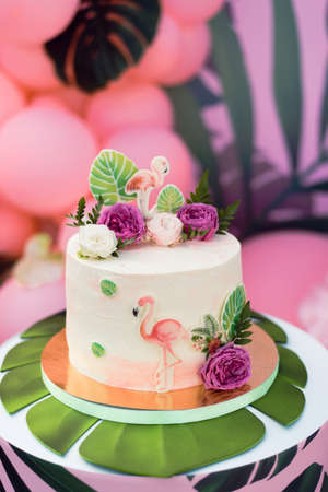 Pink cake with flamingos for the holiday. Cake with a variety of decorations, palm leaves and fresh flowers Stock Photo