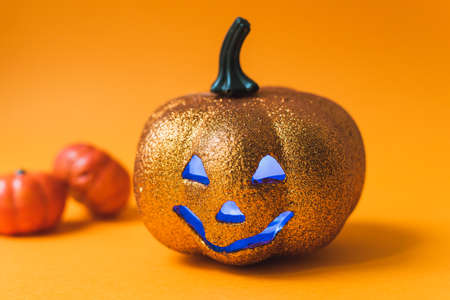 Scary shiny Halloween pumpkin toy. Jack-o'-lantern on an orange background with blue luminous eyes with a place for text.