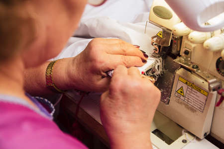 an elderly woman sews on a sewing machine. tailor embroiders in production. retired engaged favorite hobby. Stock Photo