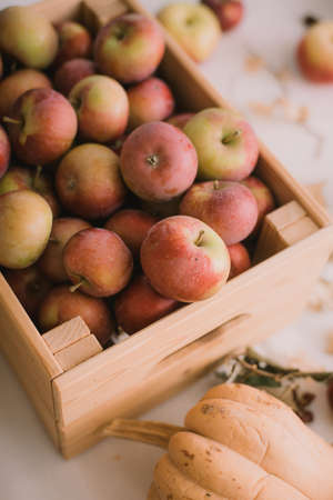 A box of rustic sweet apples on a table at home. Autumn still life