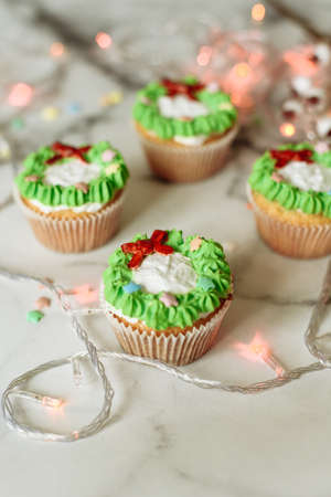 New Years sweets on a marble table. Christmas cupcakes decorated with mastic and cream. Stock fotó