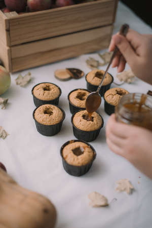 The baker creates cupcakes in molds. Filling biscuits with homemade liquid caramel. 版權商用圖片