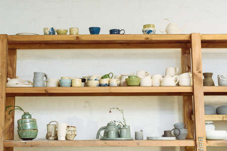 Handmade ceramic pottery in a potters workshop. Clay plates, mugs and teapots on the shelves in the workshop studio. Zdjęcie Seryjne