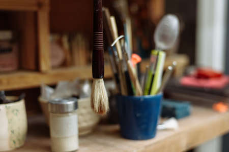 Art brushes in a potters workshop. An old brush hangs from a shelf. Stok Fotoğraf