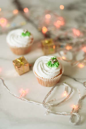 New Years sweets on a marble table. Christmas cupcakes decorated with mastic and cream. Banco de Imagens