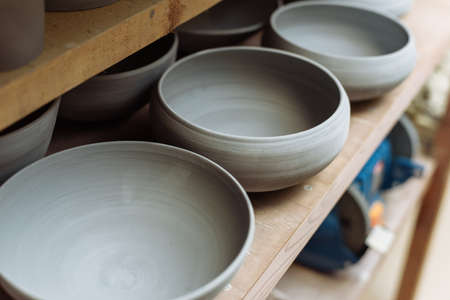 Gray handmade ceramic plates. Glazed clay plates in a pottery workshop