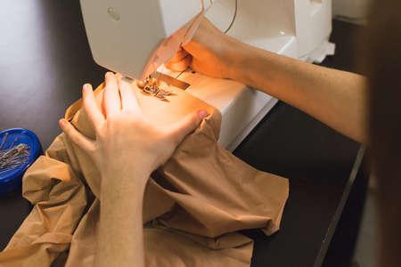 Sarta lavora su una macchina da cucire. La ragazza cuce e tiene un panno rosa. Archivio Fotografico