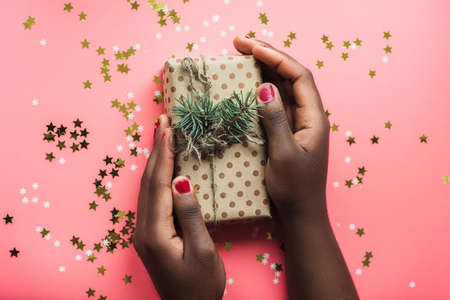 Black girl is holding a gift of Kraft paper on a pink background with confetti. Womans hands holding gift or present box decorated confetti on pink pastel table top view. Flat lay composition for birthday or wedding or christmas or Happy New Year.