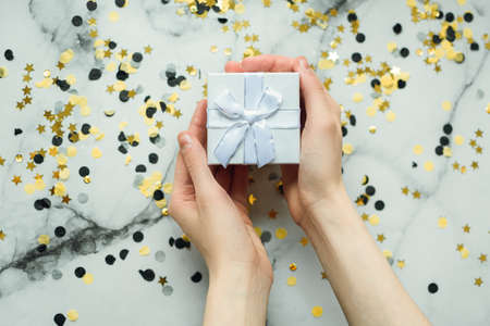 Silver gift in the hands of a girl without manicure on a gray background with gold and black confetti. Concept of the New Year and Christmas. Top View.