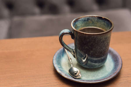 Expensive beautiful blue ceramic coffee mug on wooden table in coffee shop. A glass of black tea on a wooden surface against a gray sofa. Reklamní fotografie