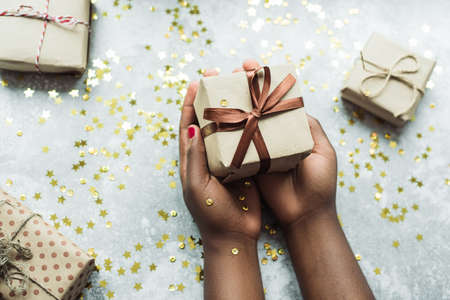 Black girl gives a gift made with her own hands. Hands holding a craft gift with a brown ribbon on a gray background with a few small gifts. Flat lay. Stock Photo