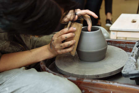 The master creates products from gray clay on a potter's wheel. Girl creates a ceramic vase.