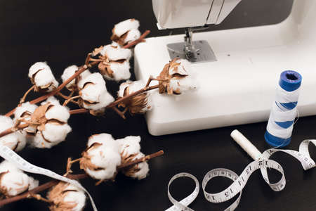 Sewing machine, centimeter, white thread and a branch of cotton flowers on a black background. The concept of sewing, small business, hobby. Copyspace, top view, flat lay.