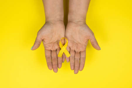 Yellow gold ribbon in the hands of a girl on a yellow background. Children cancer concept. Awareness month. Childhood Cancer Day February, 15. Stock fotó - 133828741