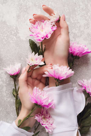 Hands of a girl with a gentle manicure in flowers on a grey background with pink chrysanthemums. The concept of caring for the skin of hands. Natural cosmetics from flower extract, beauty and fashion.