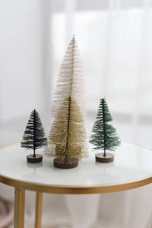 small christmas trees made of white, golden, green flocking wires on a glass white table. Stylish background, part of a modern light Christmas decor.