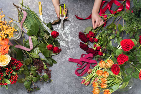 Florist creates a bouquet in a flower shop. Top view of creating a bouquet of red, orange, burgundy, yellow roses, tulips. The concept of gifts and bouquets for March 8 and Mothers Day. Cropped view of florist making flower bouquet on stone surface.
