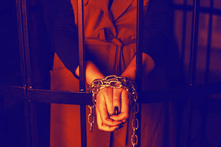 Woman behind bars. Female crime concept. Girls hands tied with chains, domestic violence.