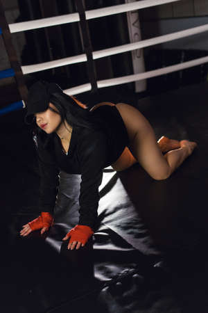 Sexy fighter girl in a black bodysuit and cap posing in a dark black boxing ring. Long hair woman fitness model. Attractive female boxer training. The concept of a healthy lifestyle.