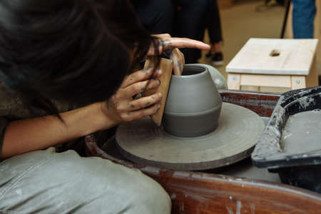 The girl sits at the Potter's wheel and creates a pot of ceramics. A Potter makes pottery out of clay behind a mechanical circle.