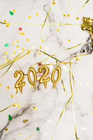 The concept of the new 2020 and Christmas. Gold numbers 2020, spangles and garlands on a marble background. top view, flat lay. Imagens