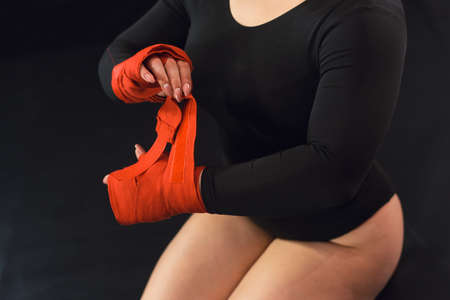 Sexy woman is wrapping hands with red boxing wraps. Strong hand and fist, ready for fight and active exercise. Women self defense. A girl in a black body wraps hands with bandages. The concept of feminism and readiness to fight.