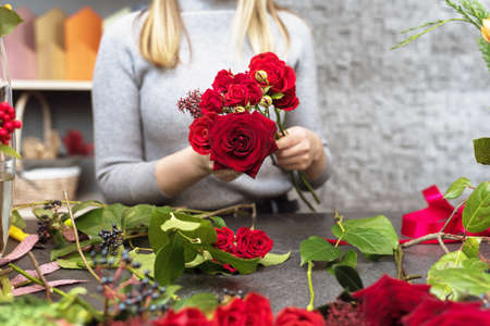 A beautiful girl collects a dark bouquet of burgundy red roses in her studio. Male florist creating beautiful bouquet in flower shop. Flowers delivery, creating order, Small business.