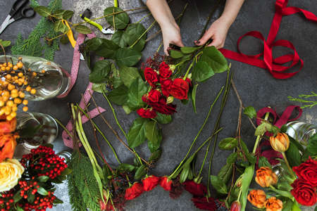 A beautiful girl collects a dark bouquet of burgundy red roses in her studio. Flat lay, top view. Flowers delivery, creating order, Small business.