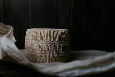 kravot cheese head on a background of dark wooden boards and parchment paper. homemade hard cheese circle in low key. The concept of homemade farm cheese made from cow's milk. Imagens