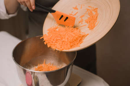 The cook adds the grated carrots to the metal bowl. Female hand put chopped carrot in wooden bowl with salad in kitchen. Cooking vegetables.